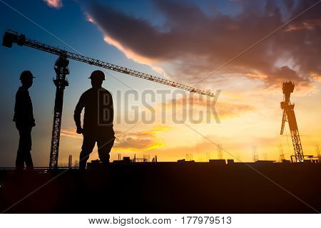 poster of Silhouette engineer construction work control and blurred tower crane background on natural sunset sky.Heavy industry and building construction work concept.