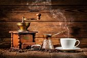 Coffee grinder, turk and cup of coffee on brown wooden background poster
