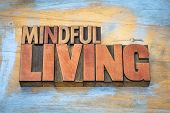 mindful living word abstract in letterpress wood type against grunge wooden background poster