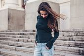Fashion model wearing blank black long sleeve tshirt posing in the city street. Casual everyday clot poster