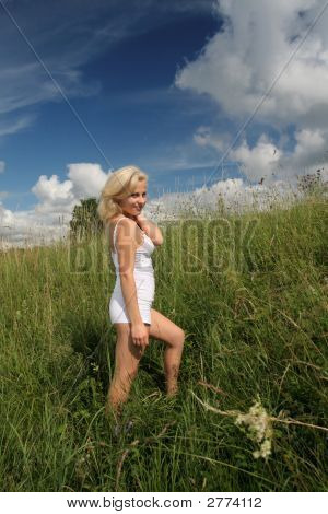 Beautifull Girl In White Dress Stands In Meadow