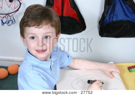 Adorable Four Year Old Boy With Big Blue Eyes Coloring At Preschool