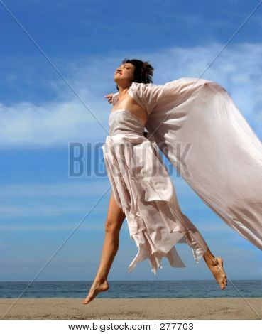 Picture or Photo of Woman jumping on the beach