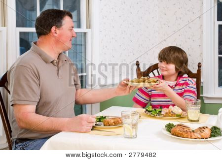 Happy Father And Son At Dinner Table