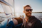 Low Angle Shot Of A Young Man Sailor Wearing Sunglasses And Gloves On A Sailing Boat At Sunset. Imag poster
