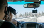 Caucasian Man Talking On The Phone While Driving A Car On A Slippery Snow Covered Road In The Taiga poster