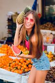 Summer Fashionable Girl Is Posing With Ananas And Slice Of Watermelon On Tropical Fruits Background. poster