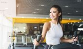 Woman Exercising At Elliptical Cardio Trainer In Gym, Copy Space poster