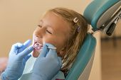 Little Girl At The Reception In The Dentists Office. Little Girl Sitting In A Chair Near A Dentist A poster