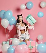 Portrait Of Young Woman In Birthday Party Holding Gift Box With Gift Present On Pastel Pink Backgrou poster
