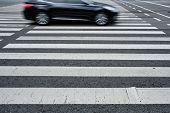 Crosswalk pedestrian crossing with blurred car on asphalt road in the street poster
