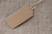 Empty Paper Tag With Rope On The Background Of Coarse Fabric. Recycled Cardboard Tag. Price Tag For poster