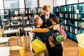Happy Schoolchildren With Backpacks Hugging Librarian In Library poster