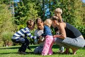 Four Kids Of Various Age With Their Mother Outside On A Grass Petting Their Pet Baby Rabbit. poster