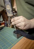 Close Up Of Hands Flattening A Rivet Into Leather Strap poster