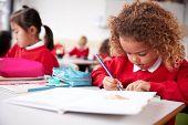 Mixed race schoolgirl wearing school uniform sitting at a desk in an infant school classroom drawing poster