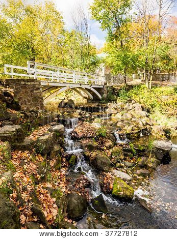 Small Footbridge Over A Small Waterfall In Autumn Landscape.
