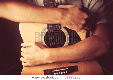 Hands Holding An Acoustic Guitar
