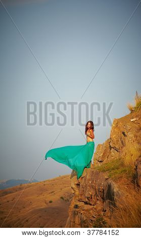 Beautiful girl standing on a precipice