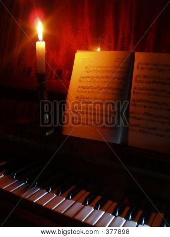 Piano And Sheet Music In The  Light Of Candle
