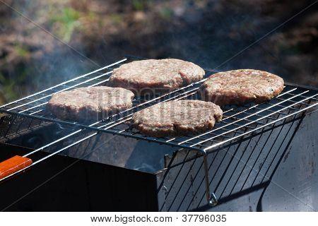 Cuatro hamburguesas en la parrilla de la barbacoa