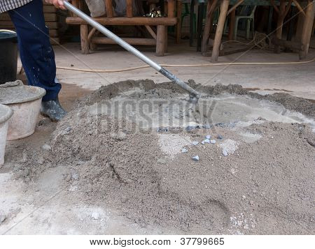 Worker is mixing cement and sand