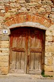 stock photo of wooden door  - An old wooden door in Tuscany Italy - JPG