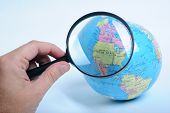 image of usa map  - Conceptual image of a hand holding a magnifier over an world globe - JPG