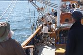 stock photo of yardarm  - KIRKLAND WASHINGTON - AUG 31 - The crew rigs the sails of the Hawaiian Chieftain as she sails on Lake Washington during a mock sea battle as part of Labor Day festivities on Aug 31 2012 near Kirkland Washington.