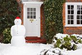 image of garden sculpture  - Real snowman outside house in winter scene - JPG