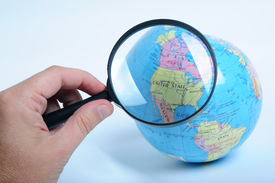stock photo of usa map  - Conceptual image of a hand holding a magnifier over an world globe - JPG