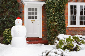 stock photo of entryway  - Real snowman outside house in winter scene - JPG