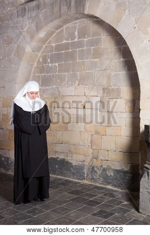 Young novice standing near the old walls of a medieval church