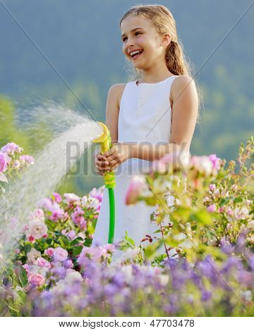 Summer garden, watering - beautiful  girl watering roses with garden hose in the garden