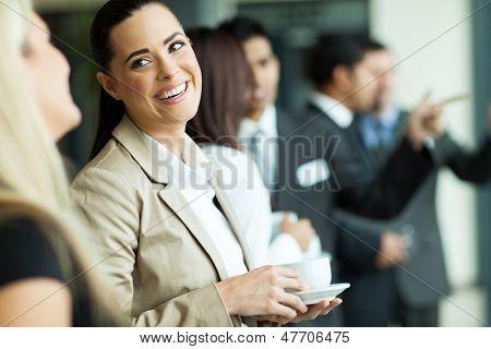 attractive businesswoman having fun conversation with colleague during break