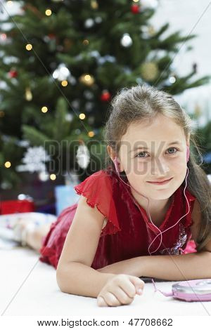 Portrait of cute little girl listening music through CD payer with Christmas tree in background