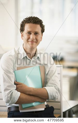 Portrait of happy young businessman with files standing by cubicle