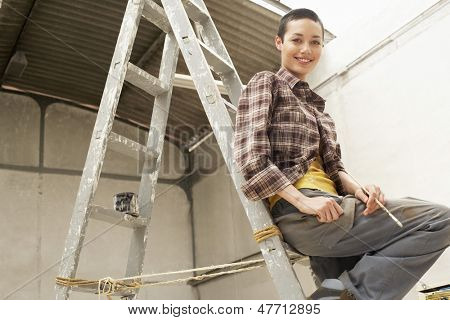 Portrait of happy young female painter sitting on ladder at work site