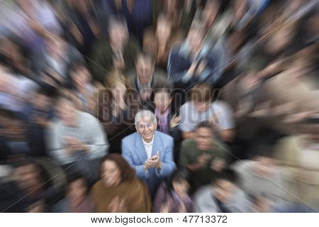 High angle portrait of senior man with crowd applauding