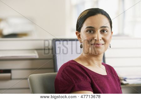 Portrait of beautiful young Asian businesswoman sitting at desk