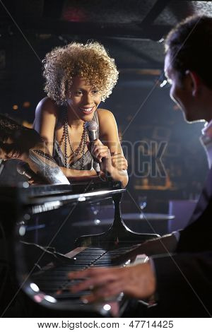 Happy female jazz singer and pianist on stage