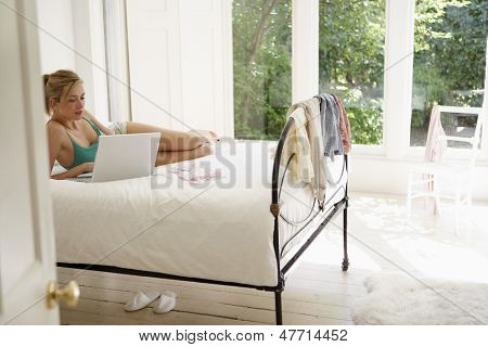 Young woman lying down while using laptop in bed