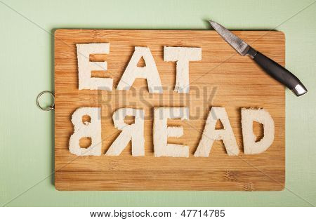 Eat Bread Text Carved Out Of White Bread Slices