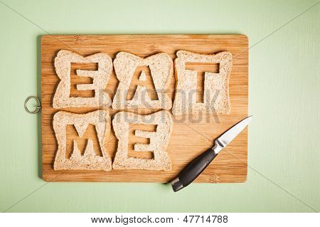 Eat Me Text Carved Out Of Brown Bread Slices