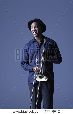 Happy African American man with trombone standing against blue background