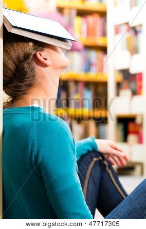 Student - Young woman in library with book learning, she is asleep