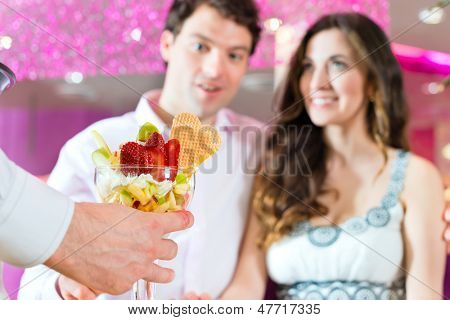 Young Couple in a Cafe or Ice cream parlor, get an ice cream served