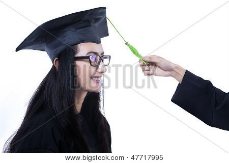 Close-up Female Graduate Fixing Mortarboard - Isolated