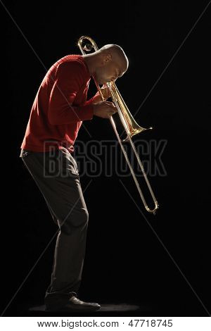 Side view of an African American man playing the trombone against black background