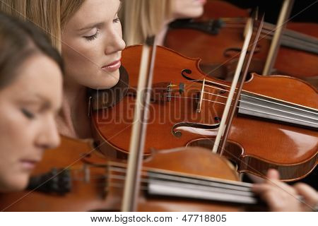 Closeup of three women playing violins in musical group